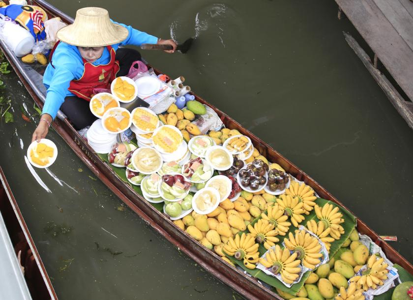 A woman offers fresh fruit for sale to tourists at Damnoen Saduak floating market in Ratchaburi province, Thailand, in 2015. Photo - EPA