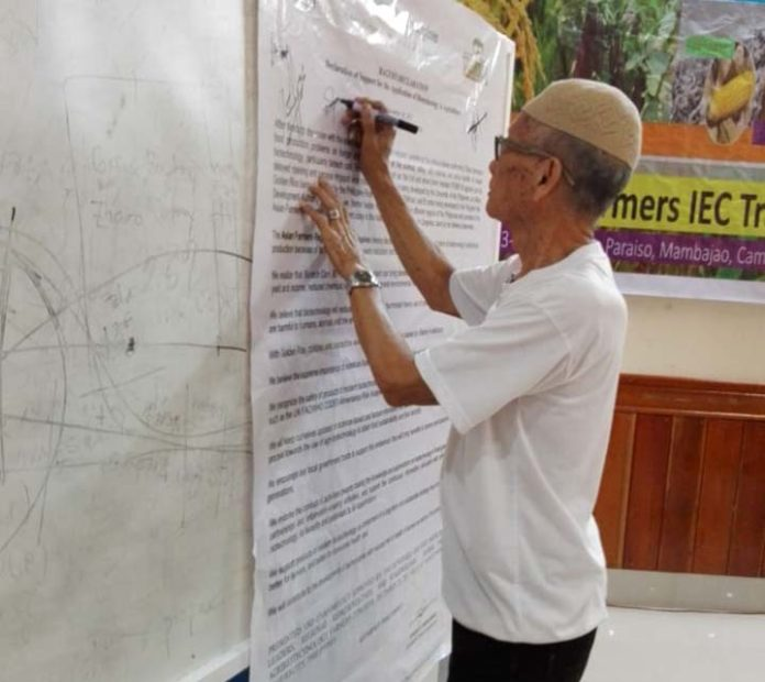 "In Photo: A farmer signs the ""Declaration of Support for the Application of Biotechnology in Agriculture."""