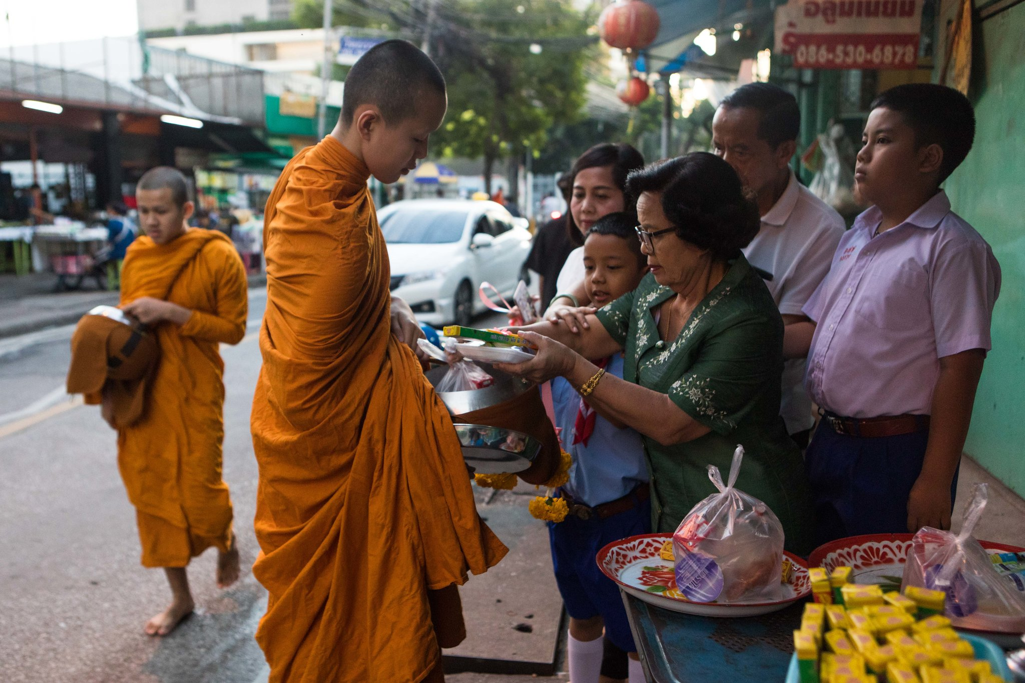 Young monks during almsgiving in Bangkok last month. Almost half of Thailand's monks are obese, and the government is urging people to give them healthier food.CreditAmanda Mustard for The New York Times