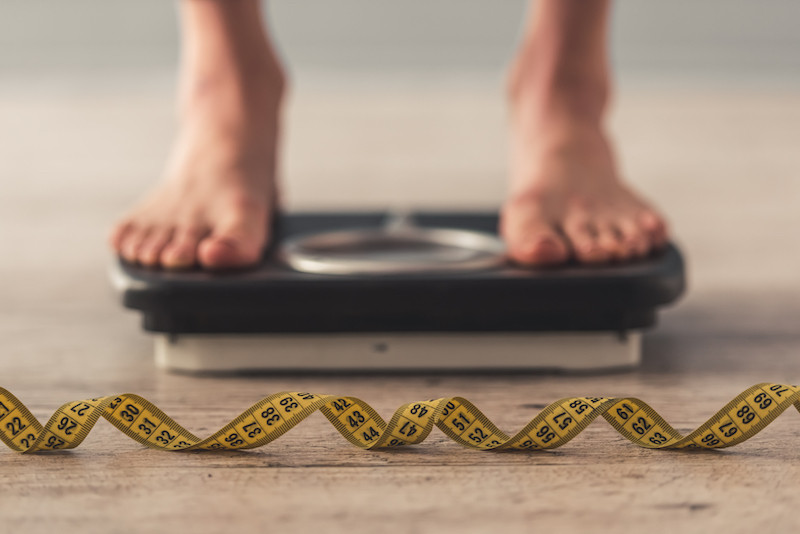 Cropped image of a person standing on weighing scales with grey background. (Shutterstock/VGstockstudio)