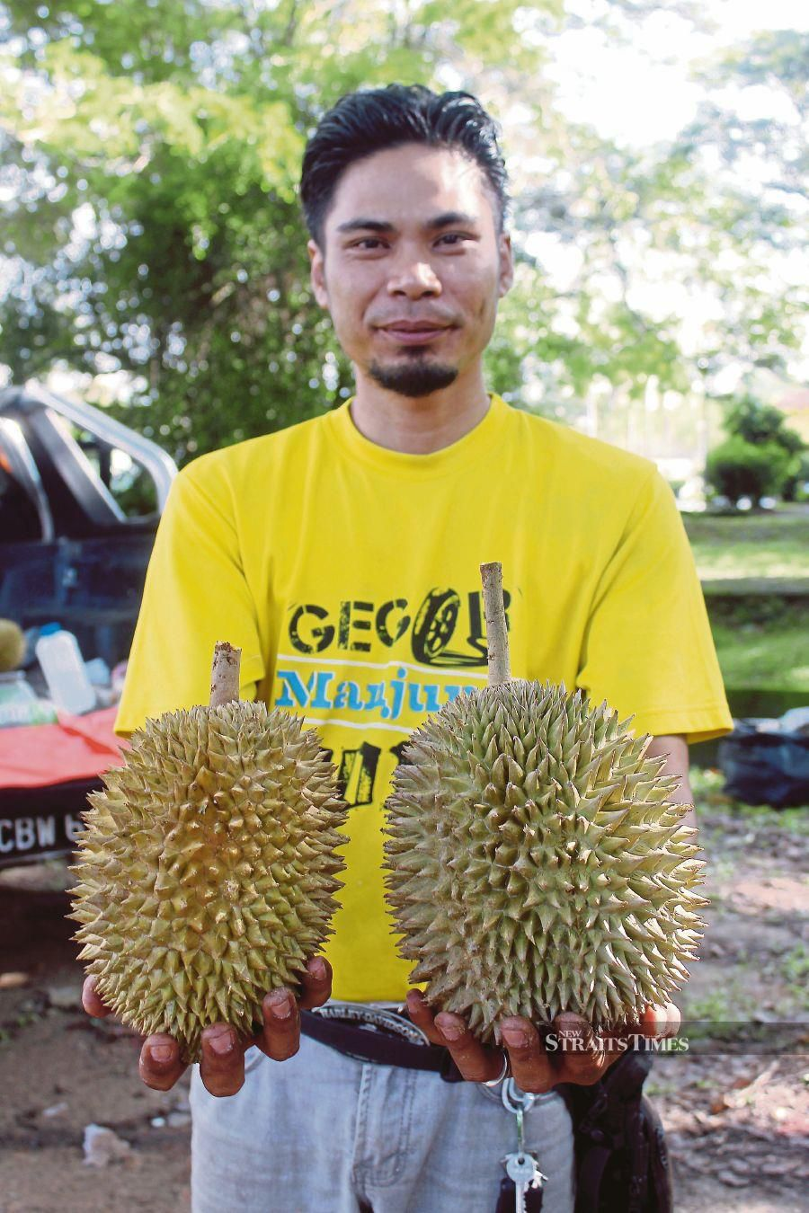 A durian seller showing off durian kampung. FILE PIC
